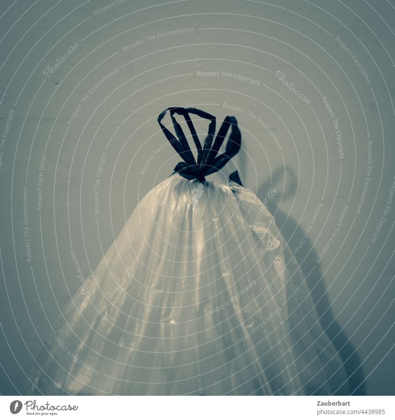 Garbage bag with bow in front of wall with shadow garbage bag Trash Recycling bag Plastic bag Bow Wall (building) Shadow Monochrome Sack Trash container