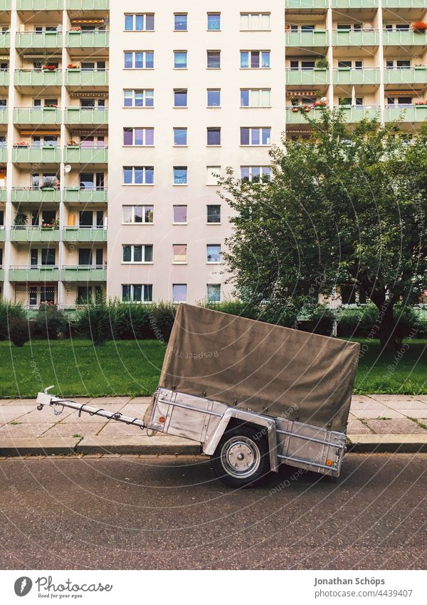 Car trailer detached on road in front of apartment block Trailer Street logistics relocation storage Transport block of flats Logistics Truck Vehicle Delivery