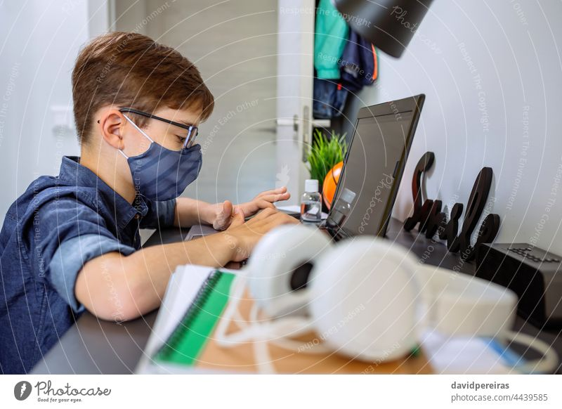 Teenager with face mask doing homework with laptop teenager school at home coronavirus home schooling e-learning boy covid-19 lockdown protective mask glasses