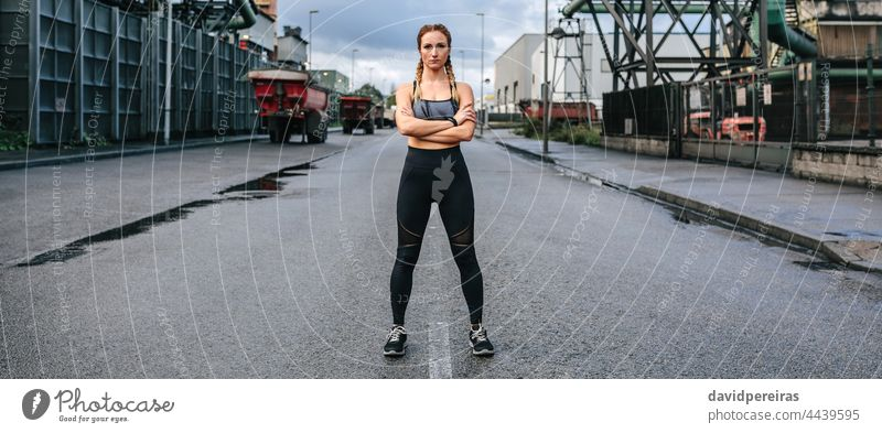 Sportswoman looking camera posing in front of a factory sportswoman runner middle road asphalt self-confident crossed arms banner web header panorama panoramic