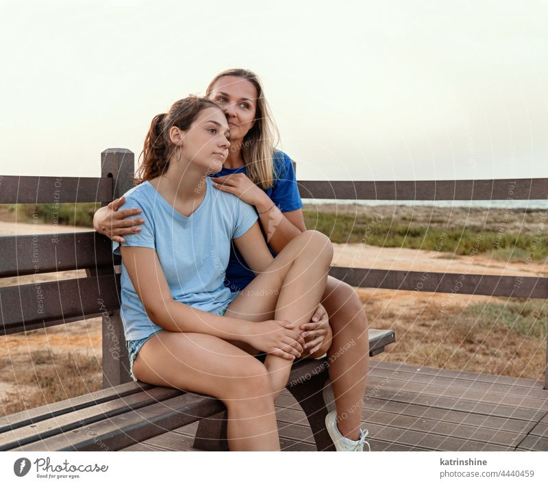 Mother and daughter sitting on a bench together at sunset woman mockup teenager embracing t-shirt hug smiling adolescent blue teen girl Caucasian park outdoor