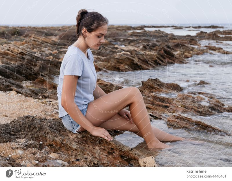 Teenage girl sitting on cliff by the sea teenager blue Caucasian rock sunset adolescent stone wearing childhood female copy space jeans lifestyle alone casual