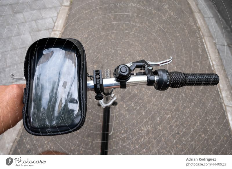 Cyclist on the bike path. First person view. Focus on the hand and the handlebars. cyclist mobile phone pov first person city ride summer road lifestyle traffic