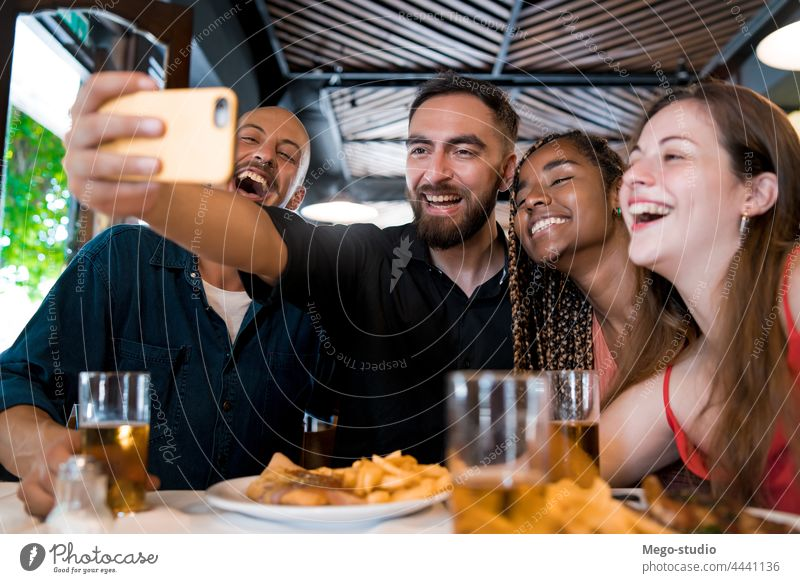 Group of friends taking a selfie with a mobile phone at a restaurant. together drink beer food meal friendship indoors enjoyment smartphone social media happy