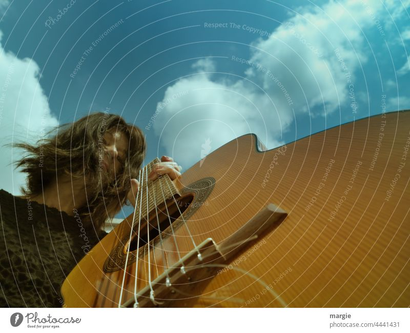Guitar player under blue sky with clouds Musical instrument String instrument Leisure and hobbies Make music Guitar string Detail Close-up Musician