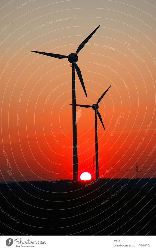 Windmills in the evening sky Red sky Back-light Sunset Evening sun Wind energy plant Generator Electrical equipment Technology Dusk