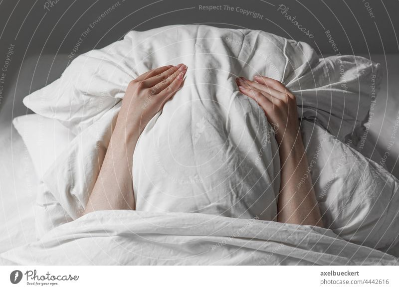 woman in bed hiding face under pillow hide cover sleep tired late riser long sleeper late sleeper unrecognizable person frustration noise anxiety stress