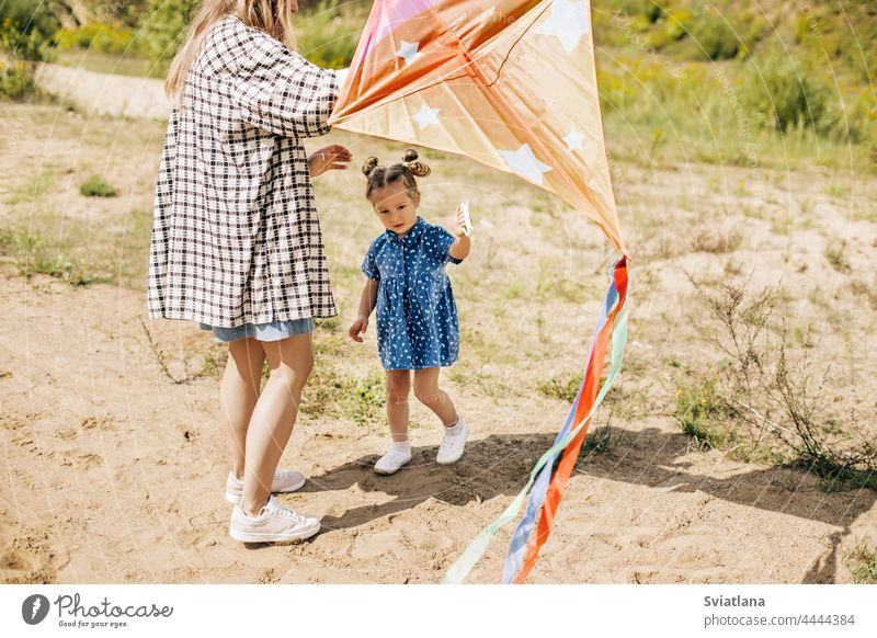 A charming little girl has fun and launches a kite together with her older sister family sisters outdoor green cute pretty best two caucasian summer cheerful