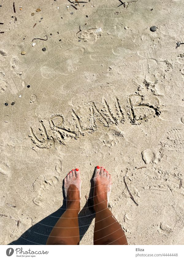 Feet standing on the beach in front of the word holiday written in the sand. vacation Sand Beach Vacation & Travel beach holiday Summer Summer vacation feet