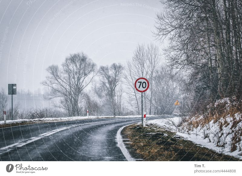 the curve of a country road in winter. In the foreground a traffic sign 70 Poland Winter Curve Street Snow Exterior shot Cold Deserted Tree Landscape Nature