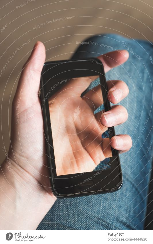 Close-up of a hand holding a smartphone, on the display of which the hand holding it can be seen translucent Cellphone Hand stop Translucent Lifestyle Telephone