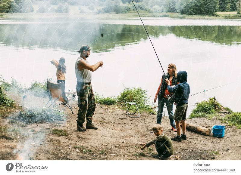 A happy family is fishing on the bank of a river or lake. Spending time together, family time, family vacation mom daughter son dad mother parenthood