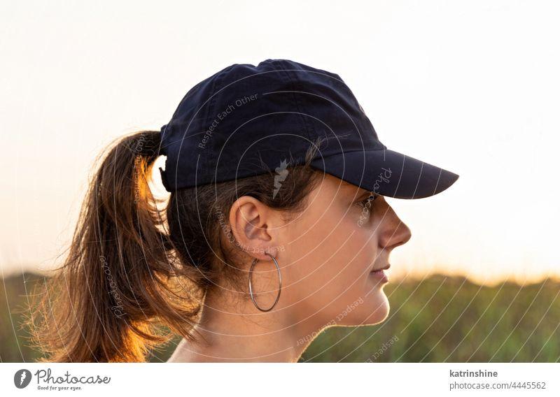 Teen girl in dark blue baseball cap at sunset outdoor teenager adolescent Caucasian mockup visor head wearing teen girl childhood female happiness pony tail