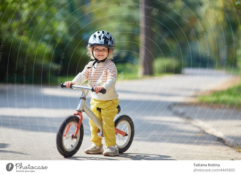 satisfied child on a balance bike in a helmet. On a sunny summer day. sport toddler bicycle baby kid park little happy fun boy girl ride play preschool young