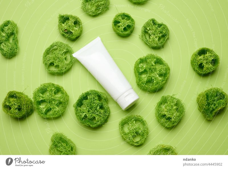 empty white plastic tubes for cosmetics on a green background. Packaging for cream, gel, serum, advertising and product promotion, top view loofah decor beauty