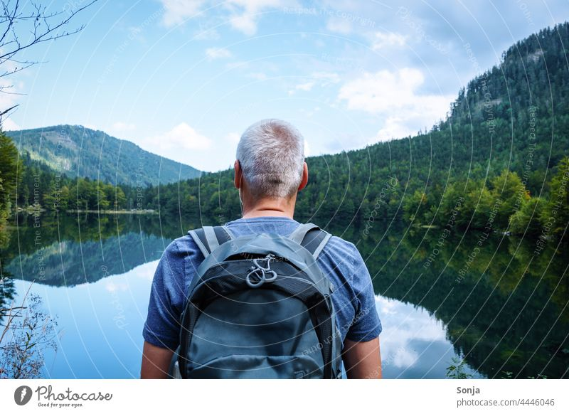 Man with a backpack stands by a lake and enjoys the view Backpack Hiking Rear view Lake Trip Tourism Vacation & Travel Freedom Senior citizen gray hair