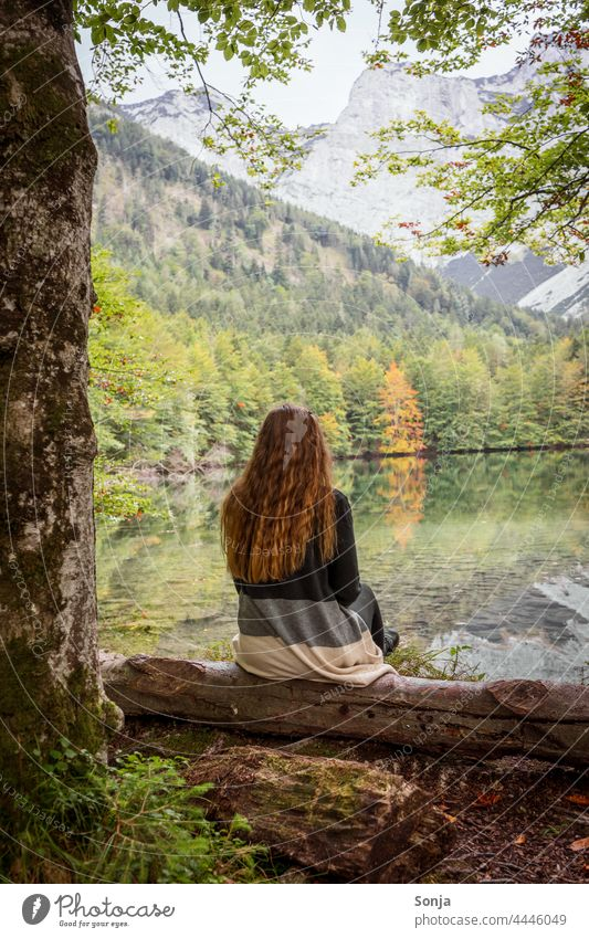 Young woman with long red hair sits by a lake and enjoys the view Woman youthful Lakeside Sit Tree trunk Forest Autumn Rear view long hairs Red lured pretty