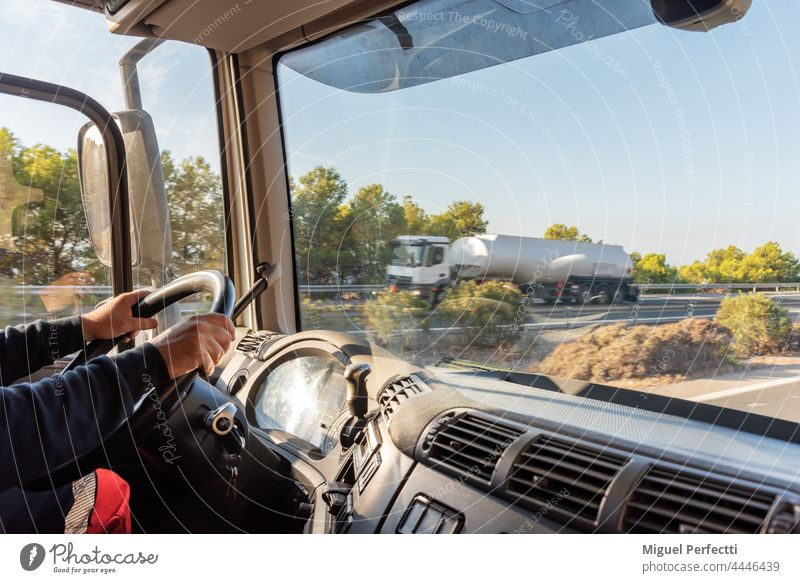 Truck driver driving on the highway, seen from inside the cab. truck driver cabin steering wheel transport working men hauler vehicle teamster transportation