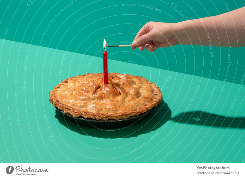 Festive apple cake with a lit candle, minimalist on a green table 4 july american apple pie autumn background baked bakery birthday bright celebration christmas