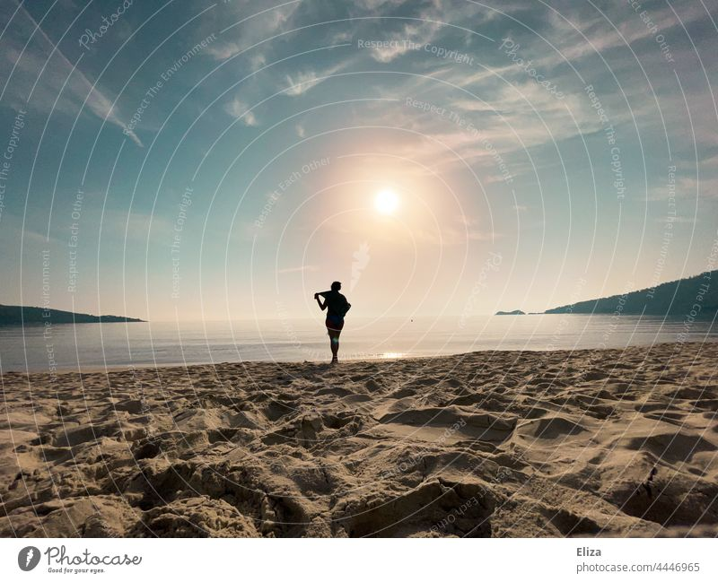 Dark silhouette of woman on beach with bright sun and smooth sea Silhouette Woman Beach Ocean Sun sunshine Black Water coast Horizon Sunrise Sunlight Wide angle