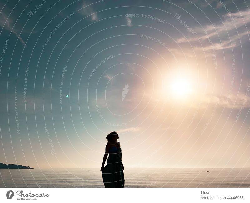 Dark silhouette of a woman by the sea looking up to the shining sun Silhouette Woman Beach Ocean Sun sunshine Black Water coast Horizon Sunrise Sunlight