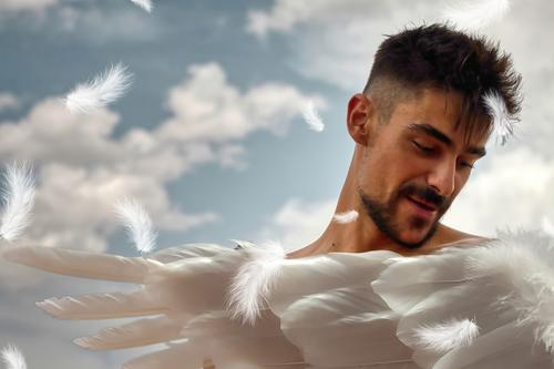 Angel. Young man with white wings and a blue sky with white clouds in the background. angel boy art fantasy magical young divine archangel angelic spirit