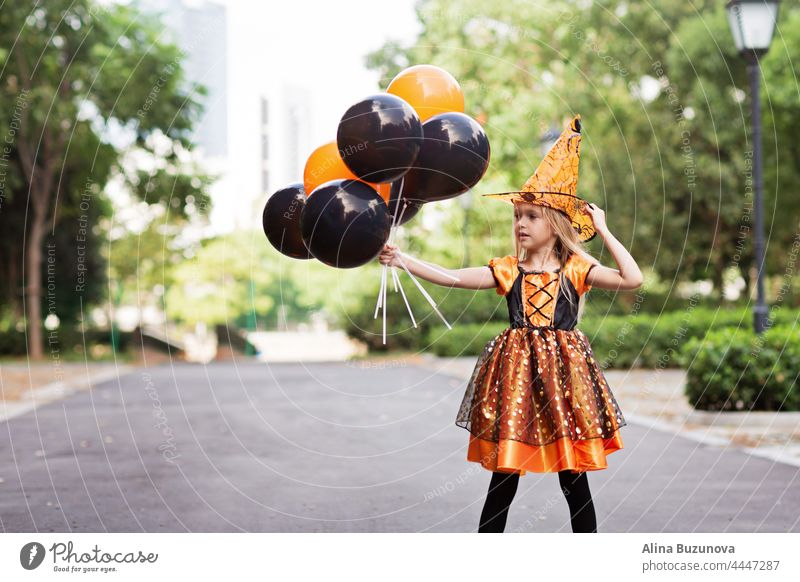 Little Caucasian Girl in costume of which holding hand hot air balloons orange and black color and celebrating Halloween halloween witch hat child girl