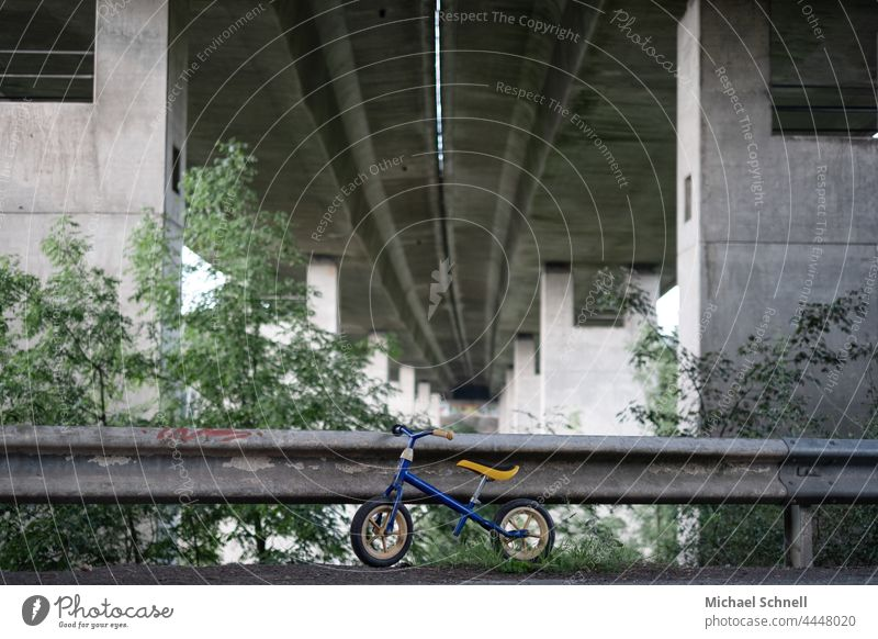 Old wheel on a guard rail under a motorway bridge impeller Child Infancy Exterior shot Movement Toddler Bicycle Playing Former Past Review Longing