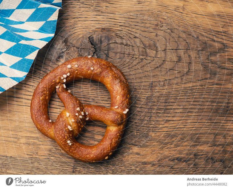Tasty pretzel with Bavarian flag on a rustic wooden table germany munich oktoberfest bavaria twisted crunchy original pastries delicious tradition invitation
