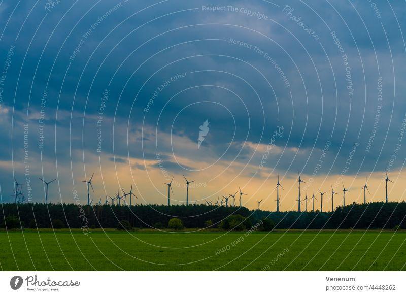 Wind turbines on a cloudy day wind turbines wind power green power electricity power generation clouds sky landscape wind farm wind energy power grid
