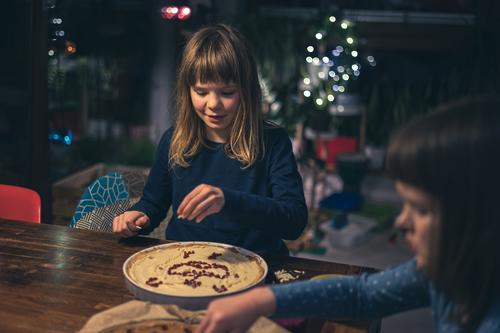 Children decorating mazurek (Polish Easter cake) at home kids family children decorated almond table handmade poland polish tradition easter cake nuts raisins