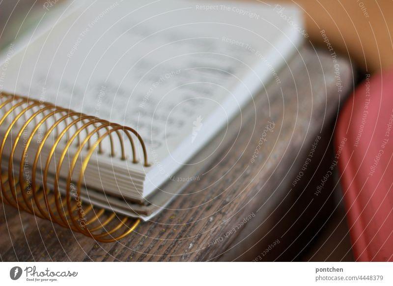 a ring pad lies on a wooden table notes, shopping list, writing Block ringblock Write write down Interior shot Living or residing spiral block Handwriting