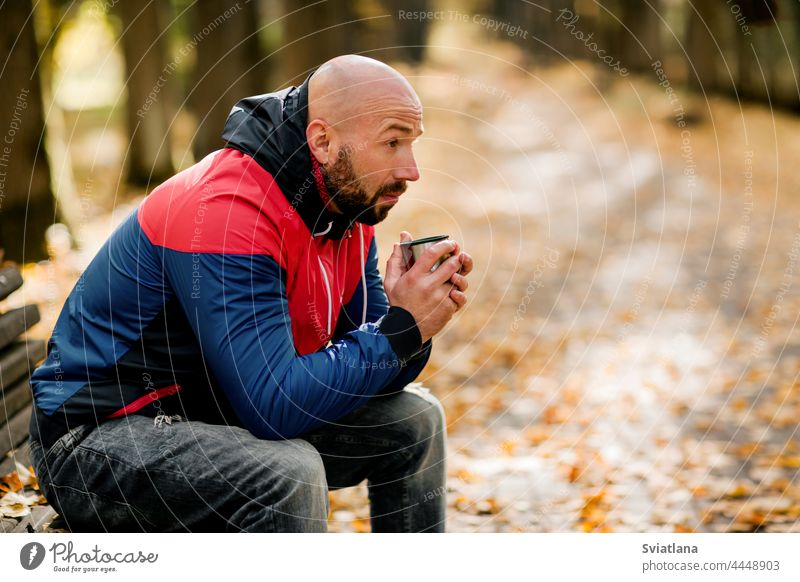 A handsome bearded man is sitting on a bench in an autumn park and drinking hot tea cup coffee fall traveler outdoor casual nature person male season people