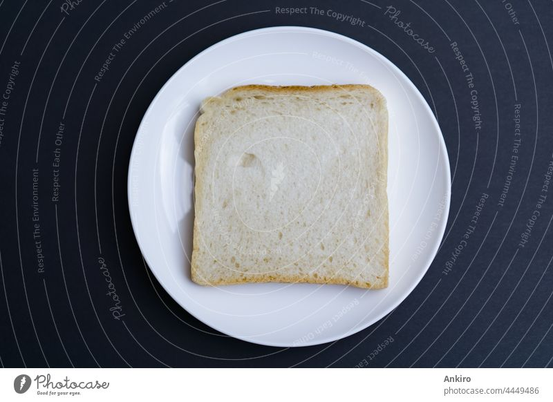 A slice of toast on a white plate, black background bread top view sandwich isolated toasted food breakfast above snack sliced cut roasted fried textured