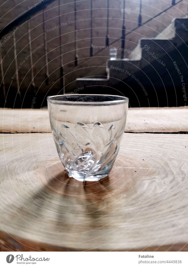 On a tree slice in front of an old staircase in a Lost Place stands an empty glass. Glass drinking glass Juice glass Tree section Wood grain Stairs Banister