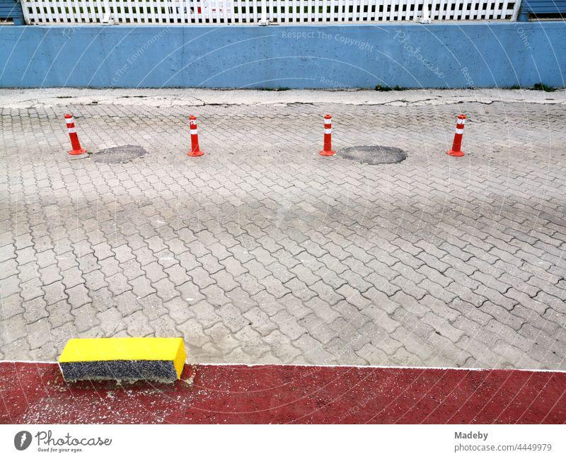 Coloured plastic road marking and bollards on grey composite paving in Sapanca near Adapazari in Sakarya Province, Turkey Street pavement paving stone Gray