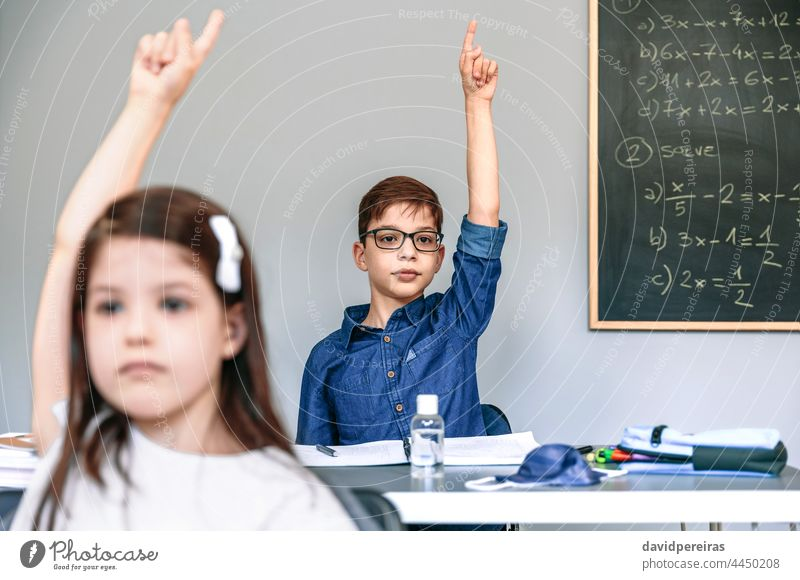 Students with mask on table raising hands at school new normal coronavirus student class participating safety people girl boy epidemic education classroom smart