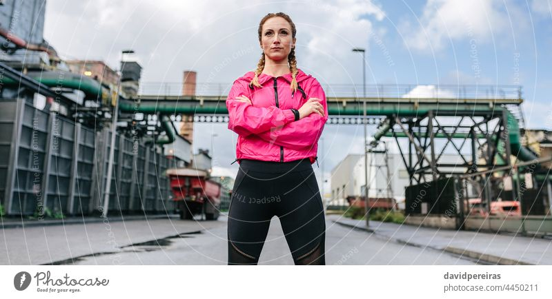 Sportswoman with crossed arms posing in front of a factory sportswoman self-confident looking straight ahead serious runner banner web header panorama panoramic
