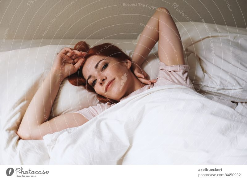 happy smiling young woman lying in bed after waking up wake bedroom morning stretch real people home adult person authentic lifestyle lady girl indoor caucasian