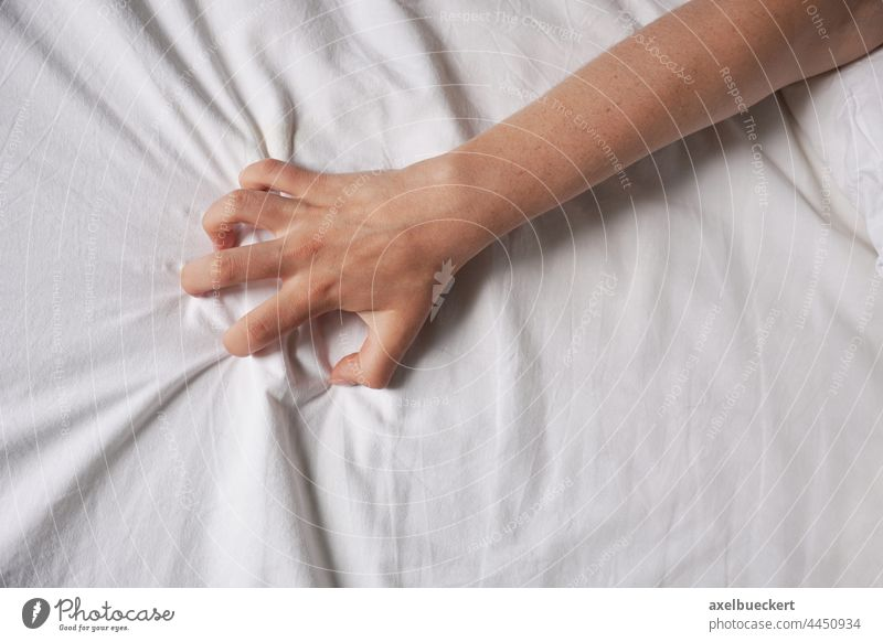 female hand grabs bed sheet grip bedsheet sex passion woman sexuality wrinkled duvet pain sensuality bedroom arm lying pleasure gripping blanket grabbing person