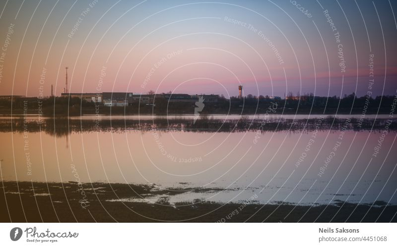 calm waveless flood water on meadow in Latvia, beautiful spring evening sunset, clear sky, factory in distance abstract afternoon background beauty black blue
