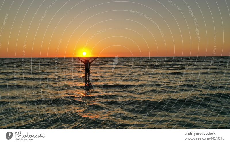 silhouette of a relaxed young girl in a bathing suit in the sea at sunrise. Happy Vacation Holiday Concept. woman happy beach sunset vacation holiday standing