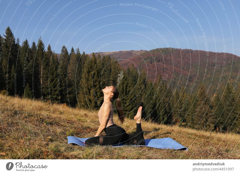Young fit woman doing exercises on yoga mat on background of sunny mountains hills. Outdoor workout, healthy lifestyle. female in sport suit is stretching in nature against the forest in the morning