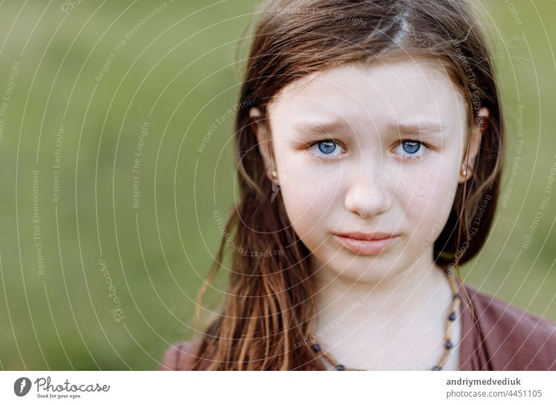 Portrait of sad crying emotional cute little girl looking at camera with face of deep sadness and sorrow outdoors. Sad child with blue eyes, copy space portrait