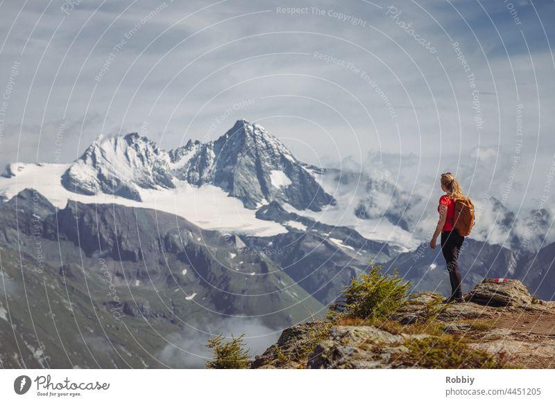 Young woman with backpack looking at the mountain Großglockner in East Tyrol Alps Grossglockner Eastern Tyrol Hiking Peak vacation Backpack Austria hike outlook