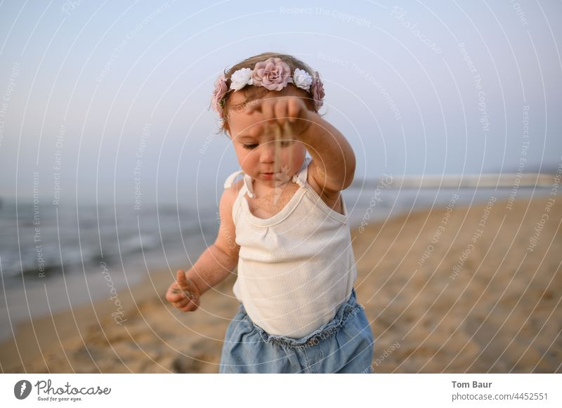Girl with flowers in her hair plays with sand on the beach - time trickles through her fingers Baby Toddler Child Hand Face Fingers 0 - 12 months Eyes Looking