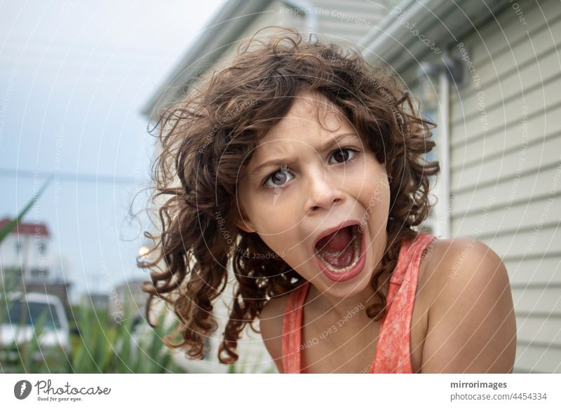 Little girl with currly brown hair making silly faces at camera with open mouth positive children summer close-up enjoyment daughter summertime sunshine