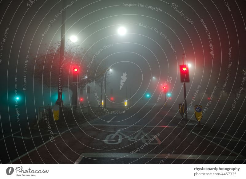 Colored traffic lights and white street lamps shine through thick fog. At a junction of two B roads in sheffield. Night time setting, so the roads are completely empty or deserted.