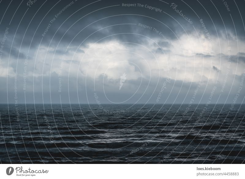 Melancholic dark blue seascape with silver shining waves during storm ocean water sky wind dramatic splash background pattern texture nature weather melancholic