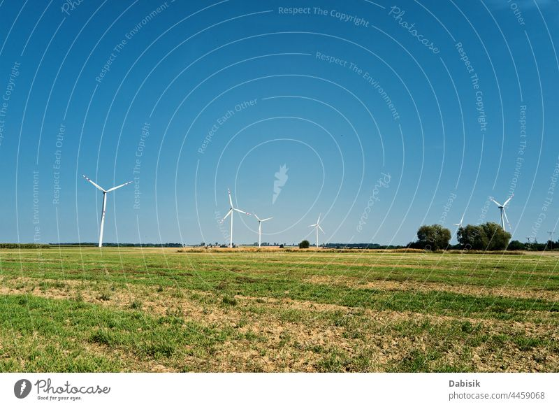 Windmill among agricultural fields. Wind turbine generator at summer day. Wind energy concept. Suistanable and renewable energy for climate protection. Green energy